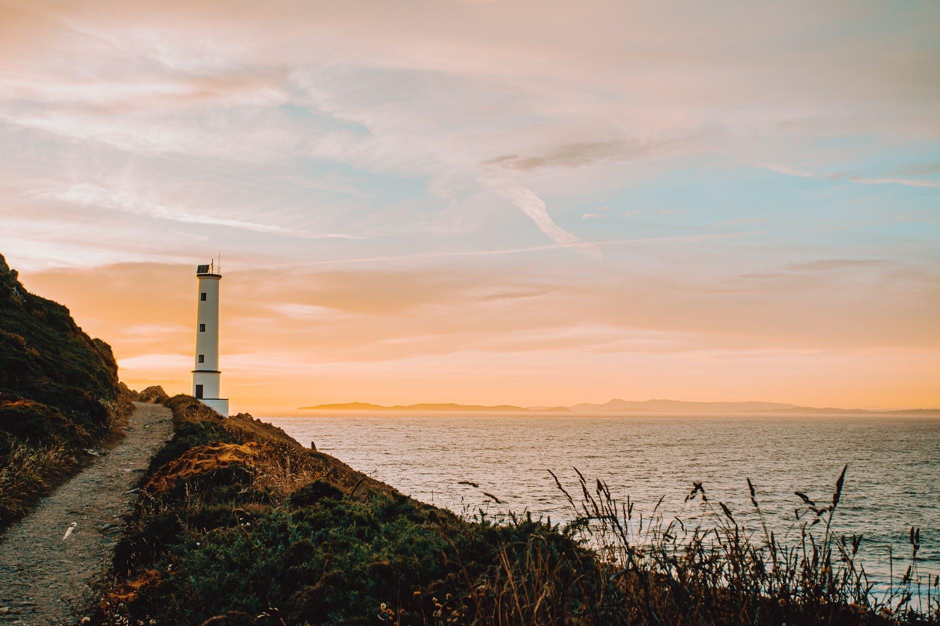 lighthouse on mountain near ocean under sky at sundown